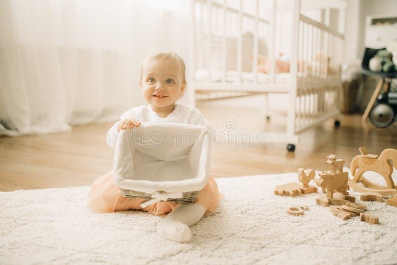 A menina da crian?a senta-se na esteira e nos jogos com cesta imagem de stock royalty free