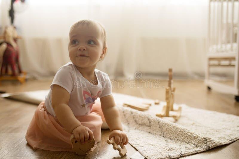 A menina da crian?a senta-se na esteira e nos jogos imagens de stock royalty free
