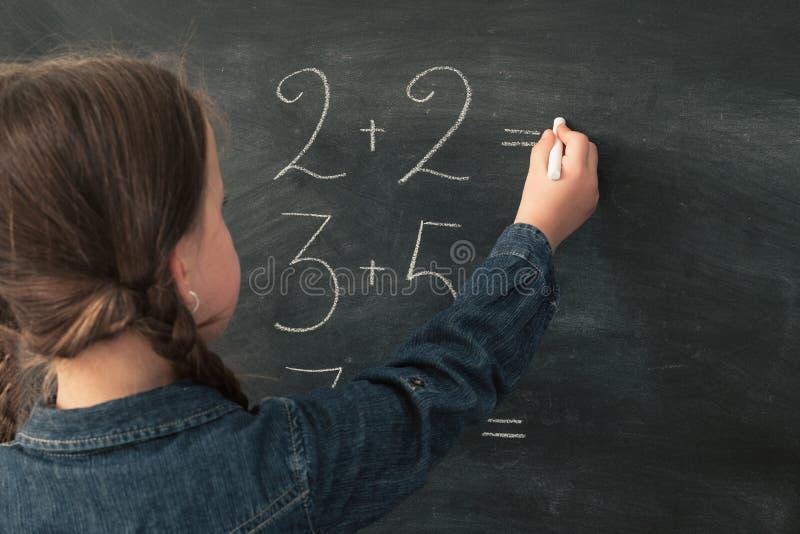 A menina da educação de escola primária faz o quadro da matemática fotografia de stock royalty free