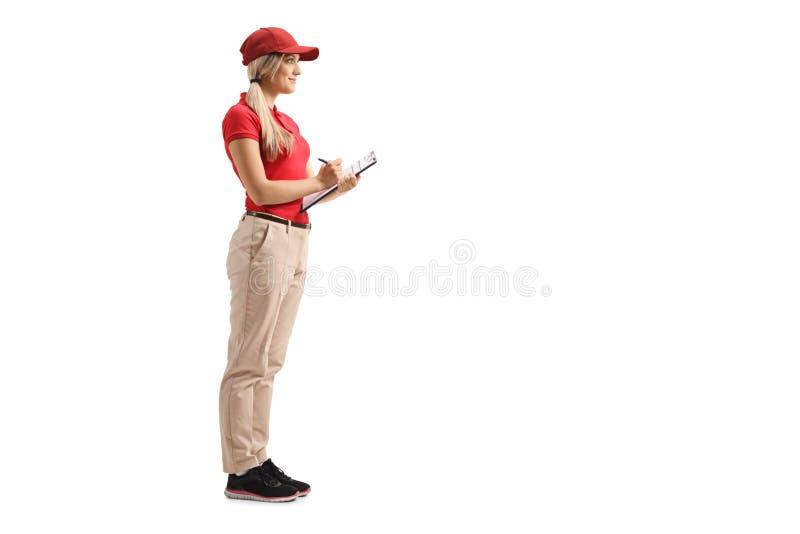 Menina da entrega em um t-shirt vermelho que está com uma prancheta imagens de stock