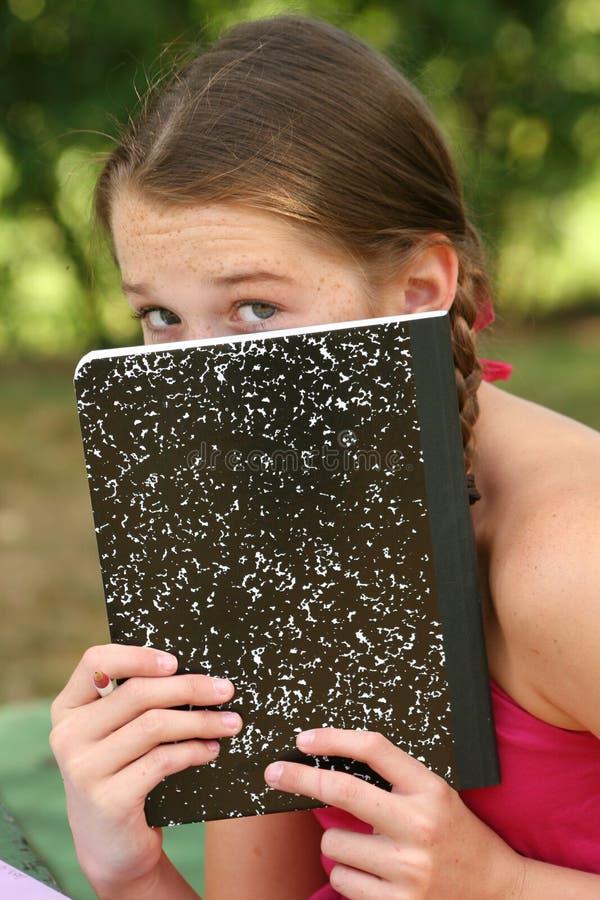 Menina da escola com um caderno ao ar livre fotos de stock