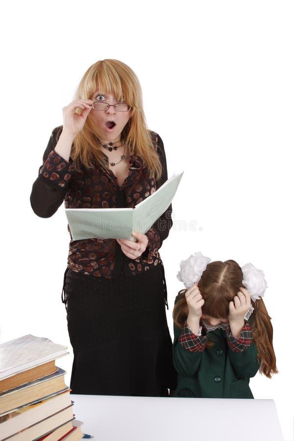 A menina da escola dá a professor um choque. Instrução. imagem de stock royalty free
