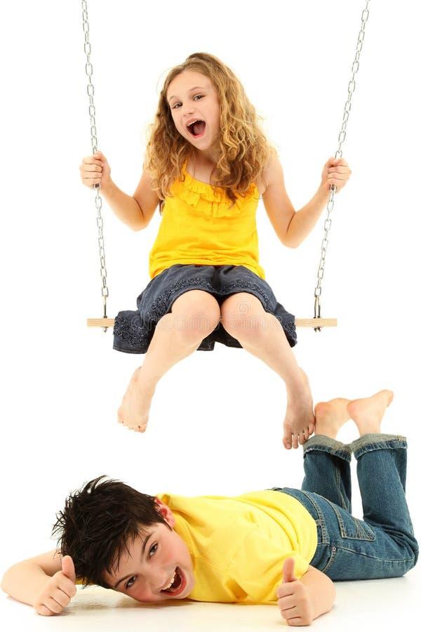 A menina da escola no balanço bate o menino para baixo na terra foto de stock