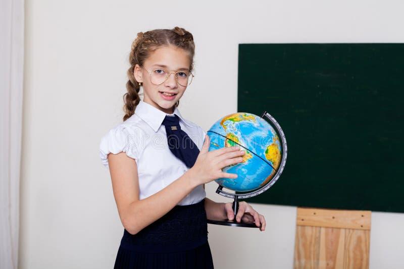Menina da escola da menina nos vidros no quadro-negro na lição na escola imagem de stock