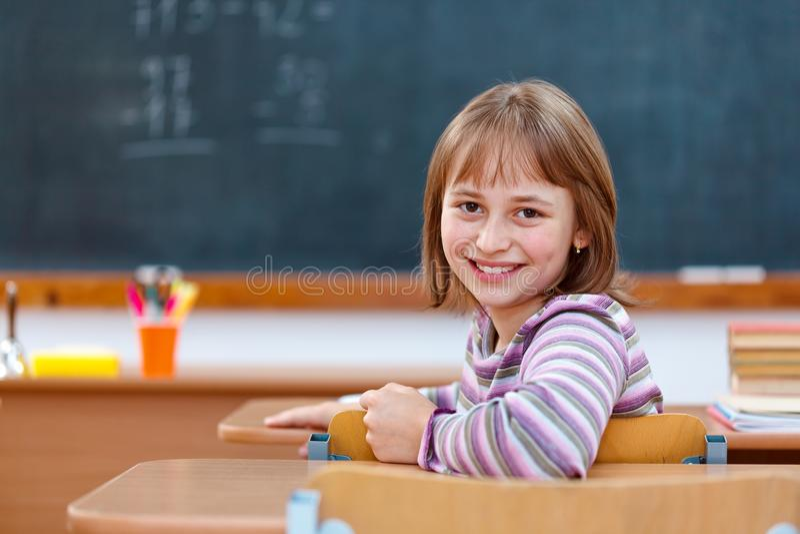 Menina da escola primária que gira para trás e que sorri imagem de stock