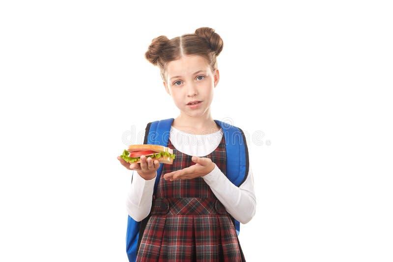 Menina da escola que come o sanduíche imagens de stock royalty free