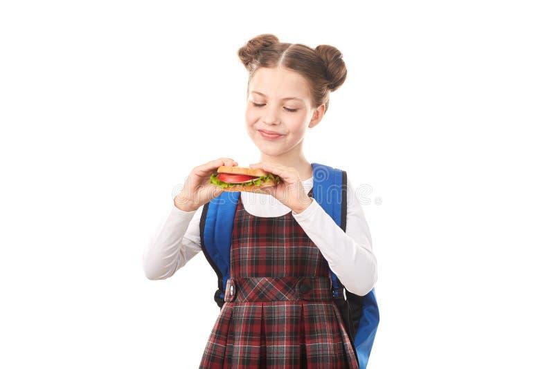 Menina da escola que come o sanduíche imagem de stock royalty free