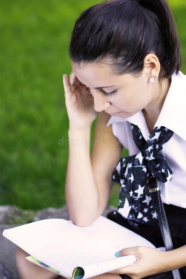 Menina da escola que estuda ao ar livre foto de stock royalty free