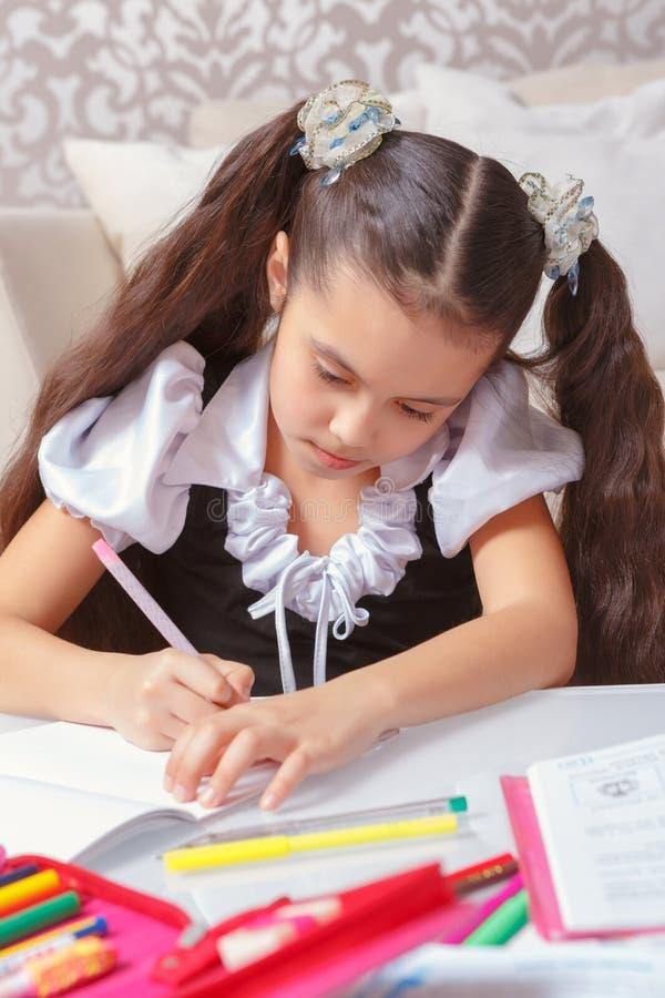 Menina da escola que faz a escrita imagens de stock royalty free