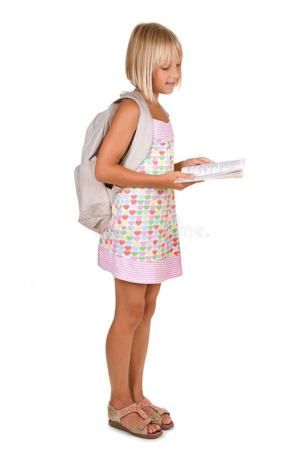 Menina da escola que lê o livro imagens de stock