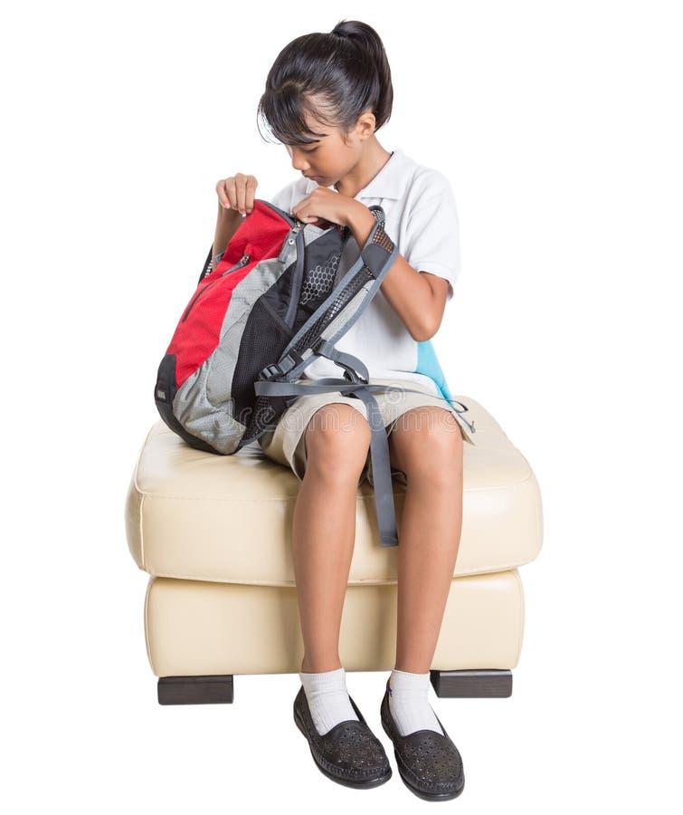 Menina da escola que senta-se no sofá com trouxa III foto de stock