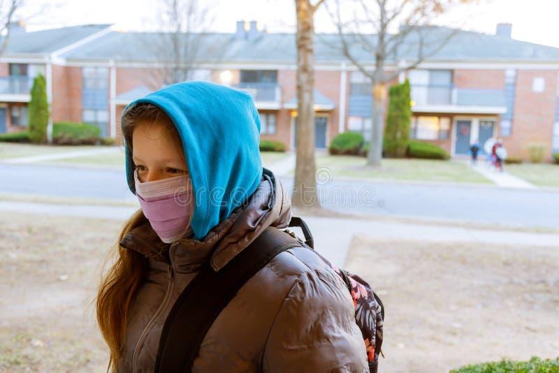 Menina da escola usando máscara bucal para prevenir a doença de Coronavírus Covid- 19 fotos de stock
