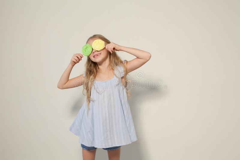 A menina da forma come um bolo do pirulito dos doces fotografia de stock