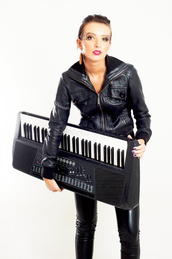 Menina da forma da rocha do punk com um piano imagem de stock