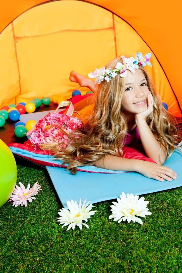 Menina da forma das crianças que encontra-se na barraca de acampamento foto de stock
