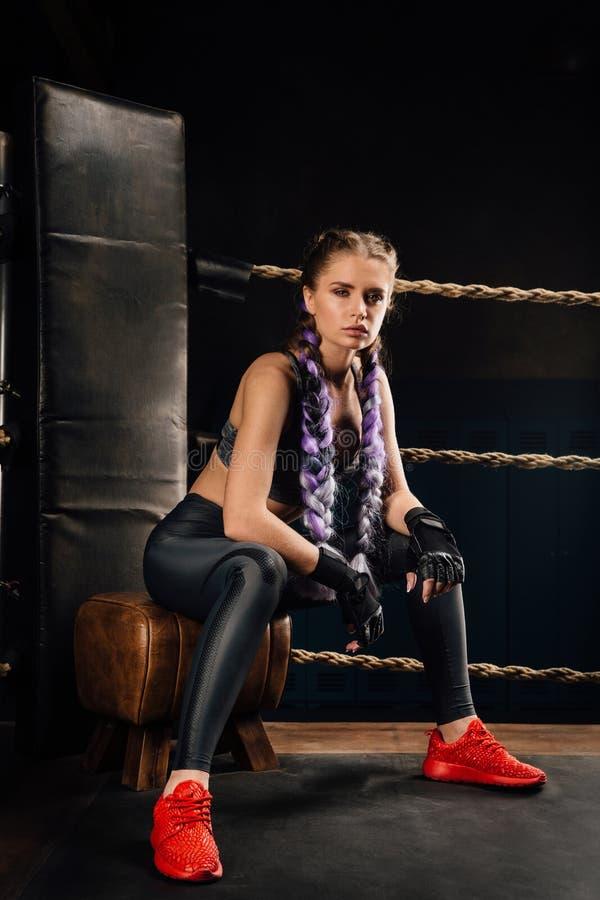 A menina da forma do encaixotamento na ruptura senta-se em uma cadeira que descansa em um anel da competição de encaixotamento fotografia de stock