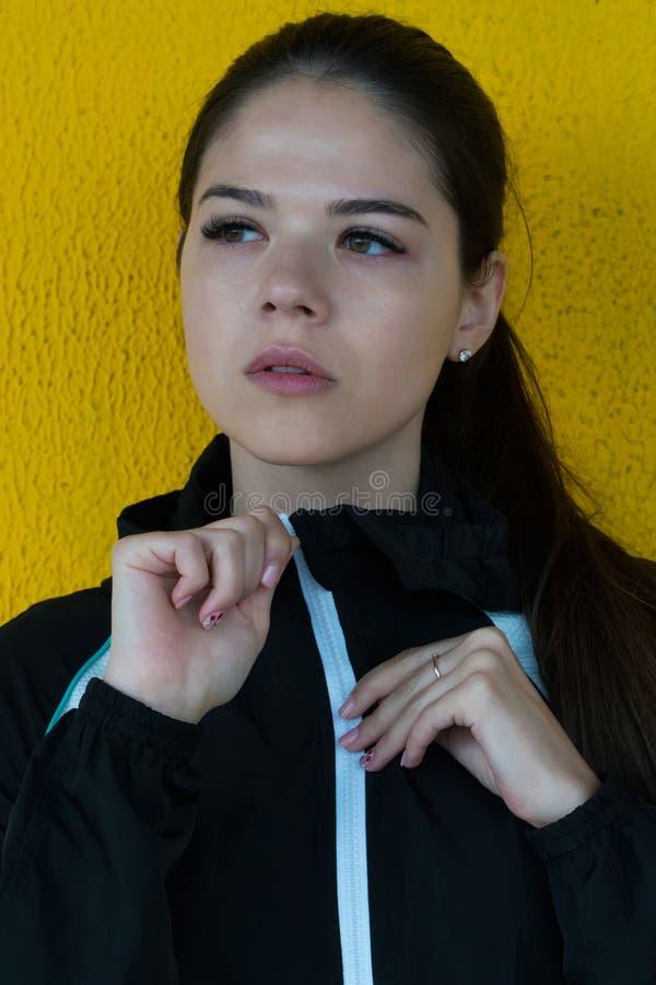 Menina da forma no sportswear no fundo amarelo foto de stock