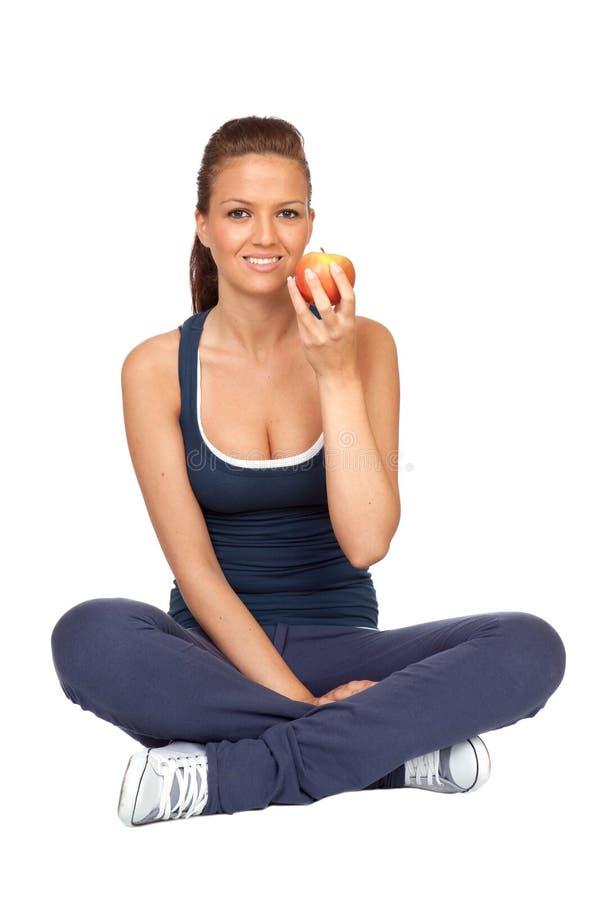 Menina da ginástica com um assento da maçã imagem de stock royalty free