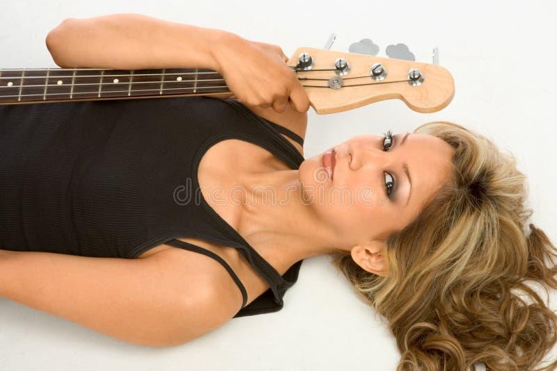 Menina da guitarra no assoalho imagem de stock