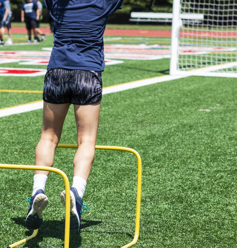Menina da High School que salta sobre dois obstáculos do amarelo do pé imagens de stock