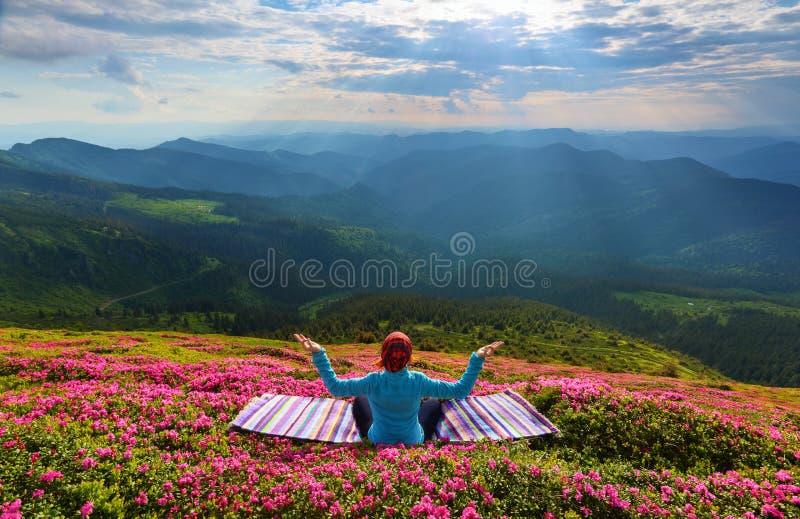 A menina da ioga está sentando-se no tapete listrado na meditação foto de stock royalty free