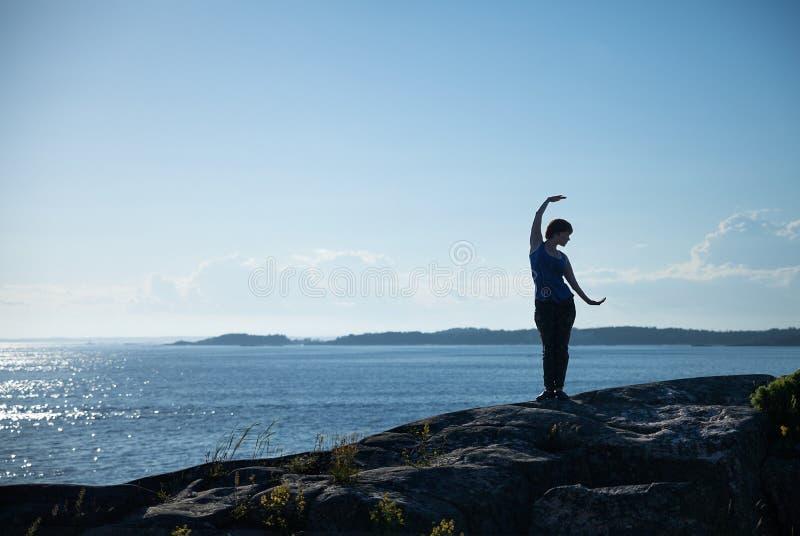 Menina da ioga na parte dianteira do mar fotografia de stock royalty free