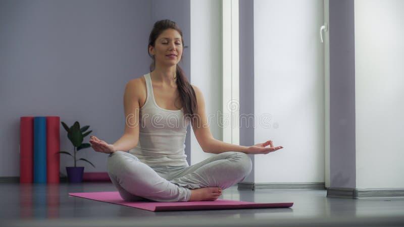 Menina da ioga que medita e que faz um símbolo do zen com sua mão fotografia de stock
