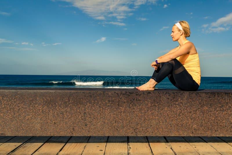 Menina da ioga que medita e que relaxa na pose da ioga, vista para o mar fotos de stock