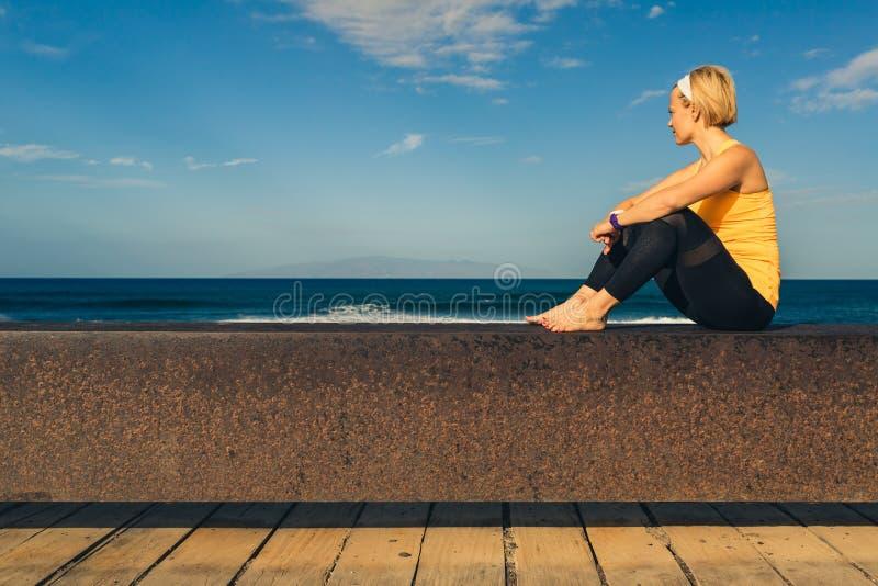 Menina da ioga que medita e que relaxa na pose da ioga, vista para o mar imagens de stock royalty free