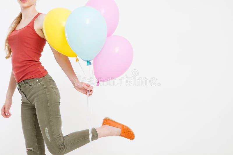 Menina da jovem mulher que corre com os balões coloridos isolados no fundo branco Copie o espaço imagens de stock