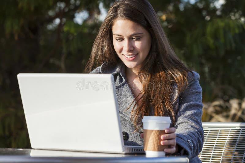 Menina da jovem mulher que usa o café bebendo do portátil imagens de stock royalty free