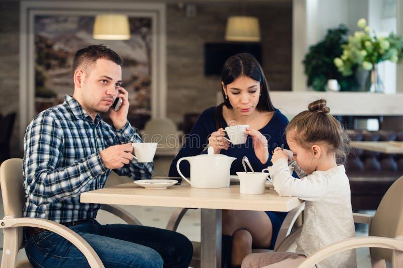 Menina da mãe caucasiano e da criança pequena no restaurante quando seu telefone celular de fala do pai ocupado foto de stock
