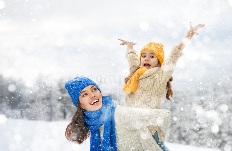 A menina da mãe e da criança em um inverno anda fotografia de stock