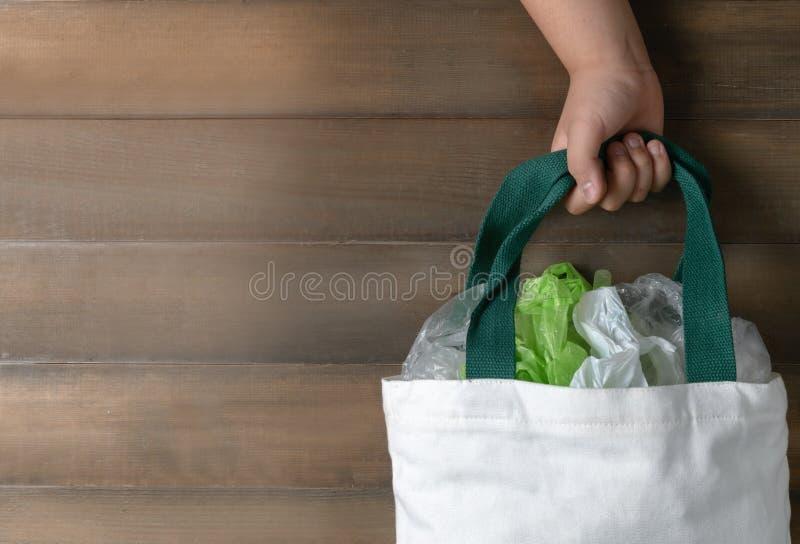 Menina da mão que guarda a sacola da lona na madeira imagem de stock royalty free