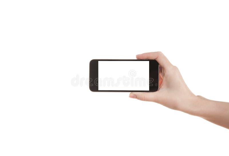Menina da mão que guarda um telefone celular fotografia de stock