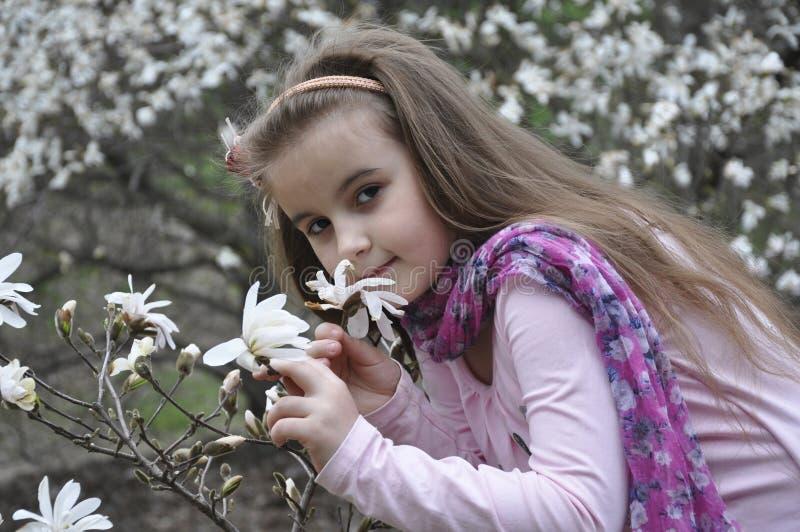 Menina da mola que cheira uma magnólia imagem de stock royalty free