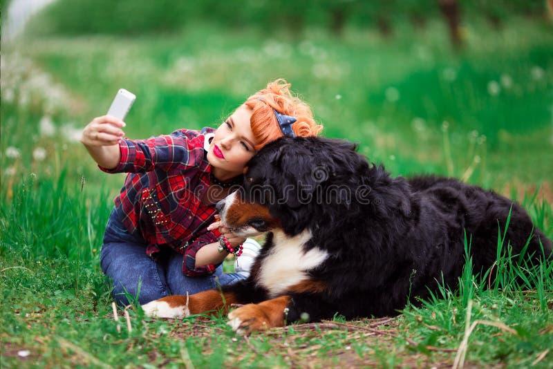 Menina da mulher com cão Berna no jardim da mola, telefone selfy foto de stock royalty free