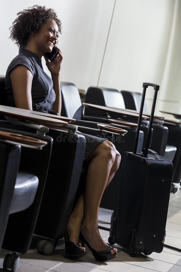Menina da mulher do americano africano no aeroporto do telefone de pilha imagens de stock royalty free