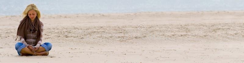 Menina da mulher na praia que escuta a música no telefone esperto fotos de stock