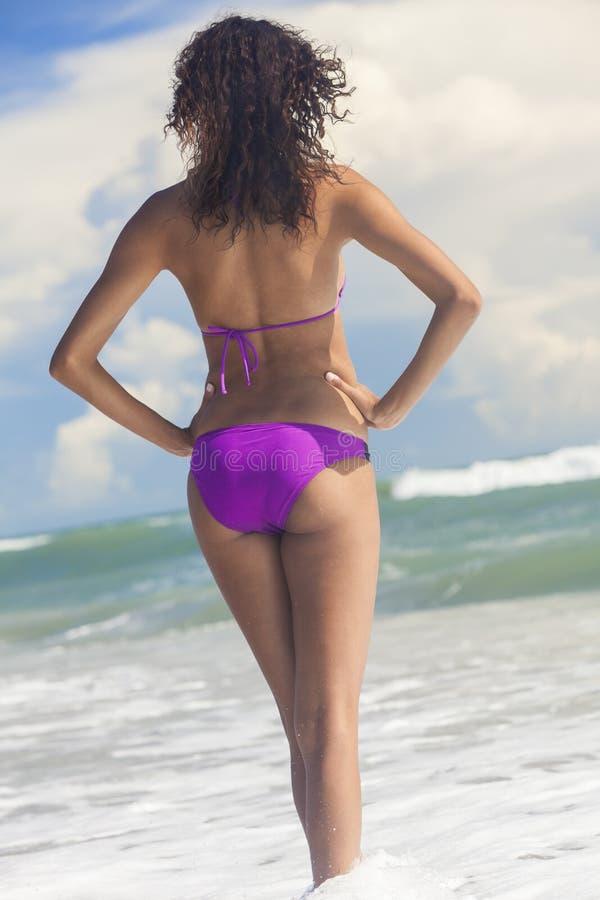 Menina da mulher no biquini que está na praia da ressaca do mar imagem de stock