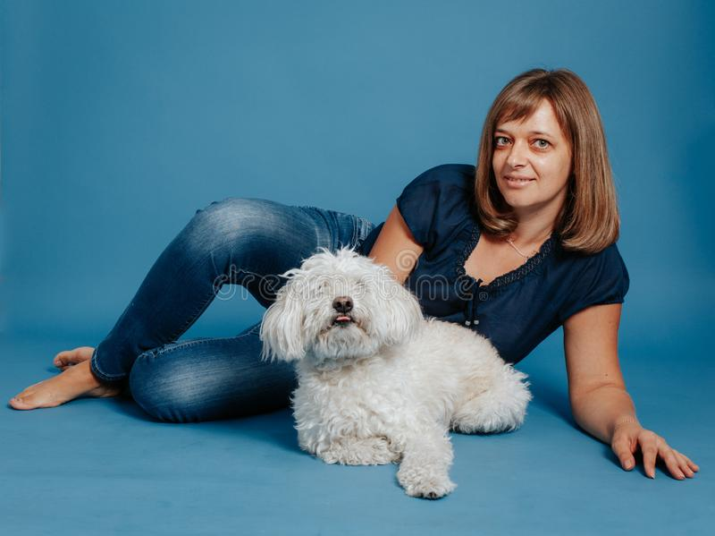 Menina da mulher que senta-se no assoalho com um cão branco fotos de stock
