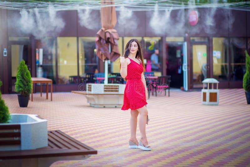 A menina da nacionalidade caucasiano em um vestido vermelho em ervilhas pequenas anda na rua da cidade fotos de stock royalty free