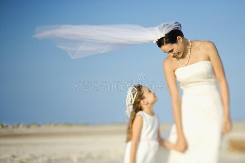 Menina da noiva e de flor na praia imagem de stock