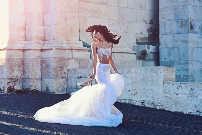Menina da noiva na cerimônia de casamento no castelo Mulher na torre antiga de pedra no verão Menina 'sexy' no vestido branco com imagem de stock