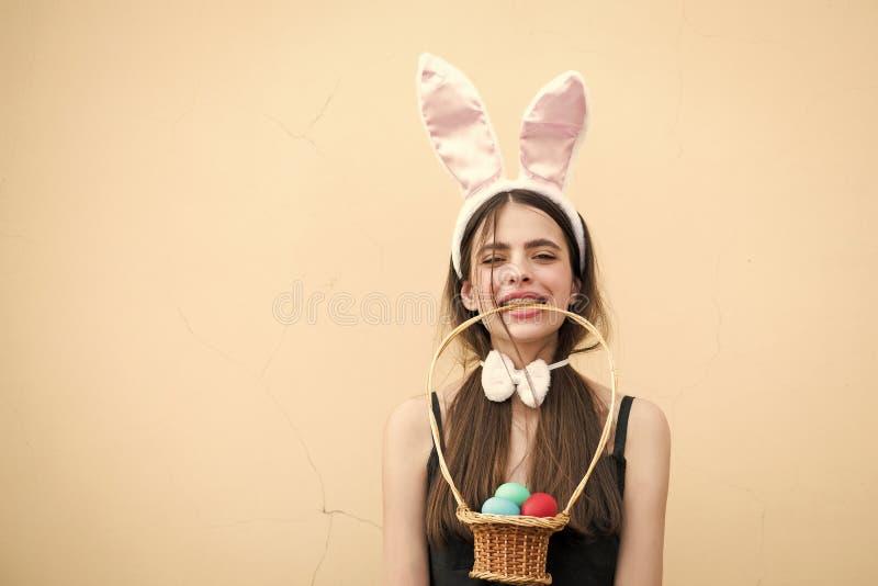 Menina da Páscoa que guarda a cesta de vime com os ovos nos dentes imagens de stock
