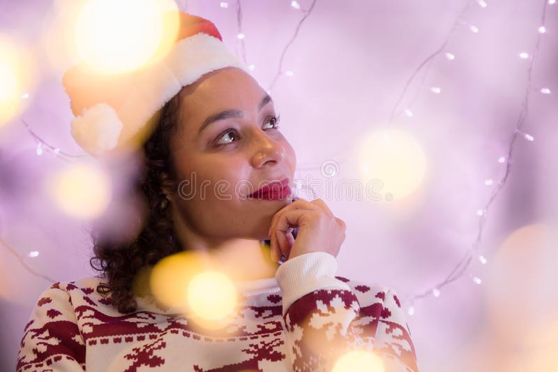 Menina da raça misturada com chapéu do Natal e a camiseta sazonal em casa fotos de stock
