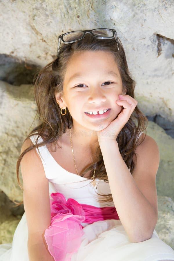 Menina da raça misturada exterior com o vestido branco cor-de-rosa alegre fotografia de stock