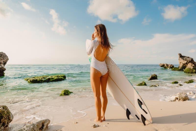 Menina da ressaca com a prancha que olha o oceano Mulher bonita do surfista na praia imagem de stock royalty free