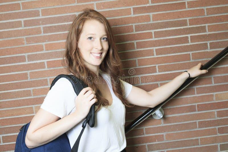 Menina da universidade/estudante universitário que olha feliz fotografia de stock