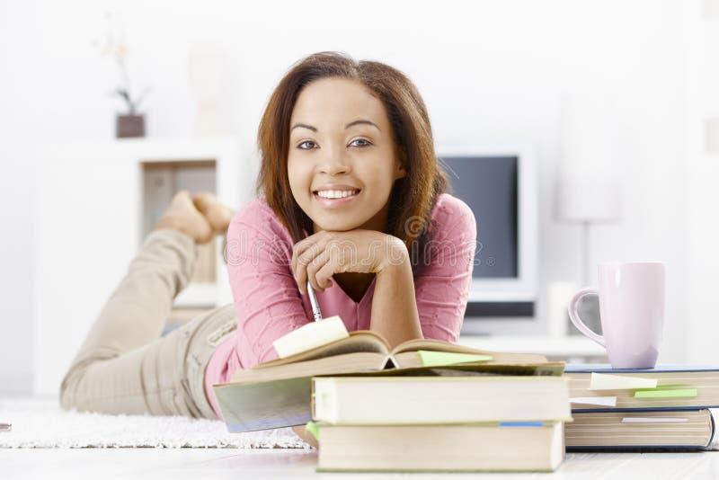 Menina da universidade que estuda no assoalho imagens de stock